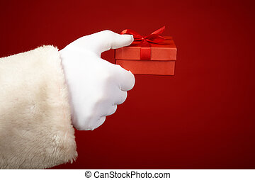 Red gift - Santa Claus hand in white glove holding small red...
