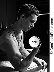 Training biceps - Black-and-white image of handsome man...