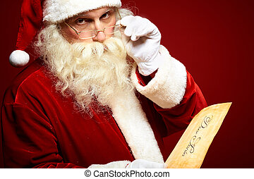 Reading Christmas letter - Serious Santa Claus with...