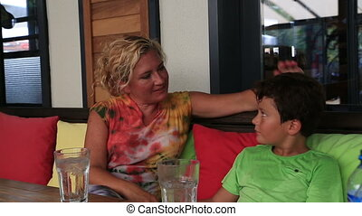 Mother and son sitting at cafe