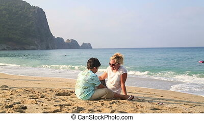 Mother and son sitting at beach and talking