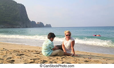 Mother and son sitting at beach