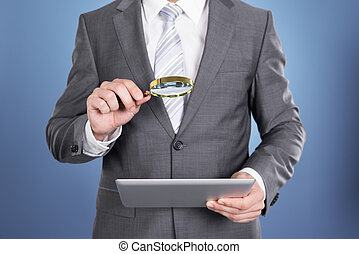 Auditor holding magnifying glass and tablet. Over blue...