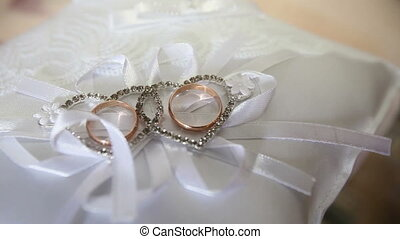wedding rings on a small pillow with bows