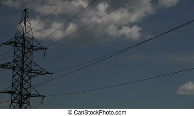 high-voltage wires on the mast sky with clouds -...