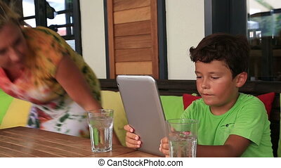 Mother and son with digital tablet at cafe