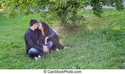 Man and woman sitting together on the grass in the park