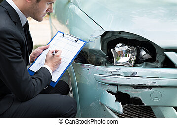 Insurance Agent Examining Car After Accident - Side view of...