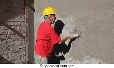 Construction site facade making - Worker spreading mortar...