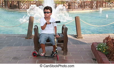 Child with scooter sitting on the park bench