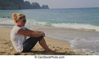 Portrait of a worried woman sitting on the beach