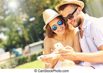 Couple with smartphones in the park - A picture of a happy...