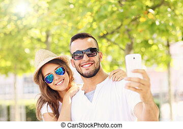 Happy couple taking selfie in the park