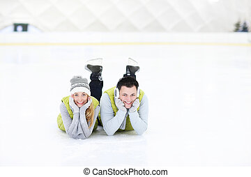 Cheerful couple lying on the skating rink - A picture of a...