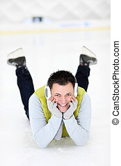 Cheerful man lying on a skating rink - A picture of a happy...