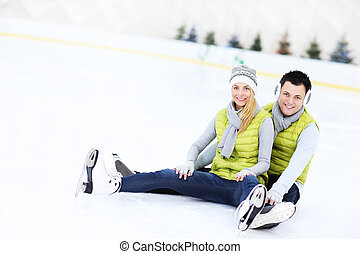 Cheerful couple sitting on the skating rink - A picture of a...