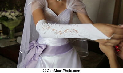 bride dress glove on his hand and helps her girlfriend