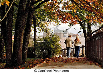 Man and Woman walking in autumn park - Man and woman walking...