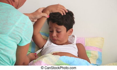 Sick child lying in bed - Sick child lying in bed with a...