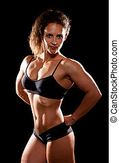 Sporty muscular woman on black background.
