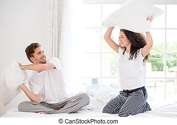 Couple pillow fighting - Young couple having fun while...
