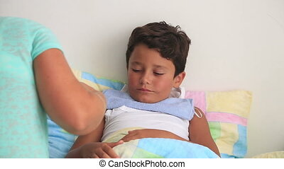 Sick child lying in bed - Sick child takes medicine in bed...