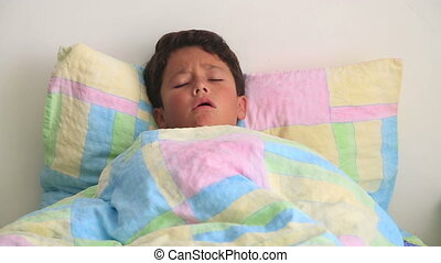 Sick child lying in bed and coughing