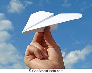 child hand with paper plane against blue sky...