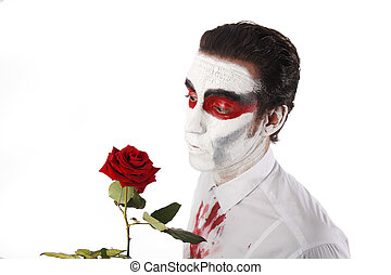 Man with white mascara and bloody shirt holds red rose in...