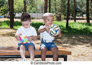 Little boys: African American and caucasian with soccer ball...