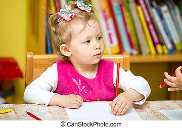 Child girl drawing with colorful pencils in preschool at the...