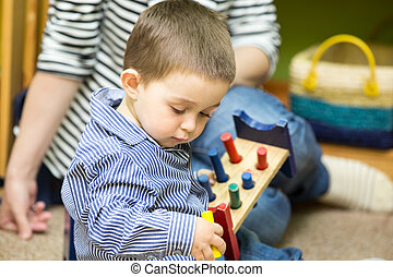 Little child boy playing in kindergarten in Montessori...