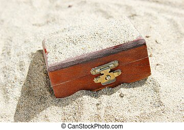 Treasure Chest Buried in Sand - A closed wooden treasure...
