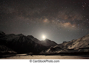 Night sky and stars passing by behind mountain Taboche,...