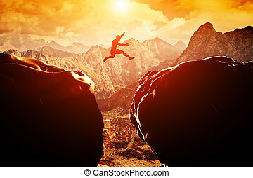 Man jumping over precipice between two rocky mountains at...
