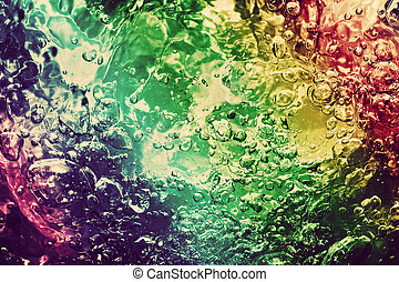 Colorful splashing, pouring water with bubbles. Colors of...