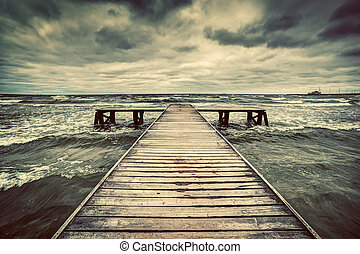 Old wooden jetty during storm on the sea. Dramatic sky with...