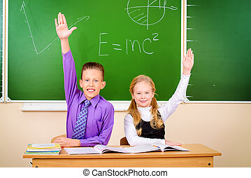 answering pupils - Students sit at their desk during a...