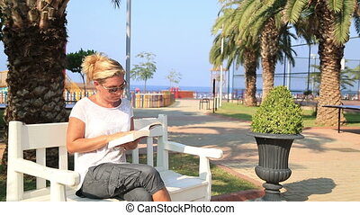 Woman reading a book on park bench
