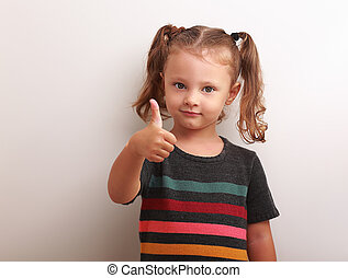 Happy kid girl showing thumb up sign and smiling