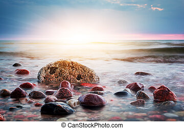 Dramatic colorful sunset on a rocky beach. Baltic sea....