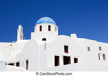 White buildings and church with blue dome in Oia or Ia on...
