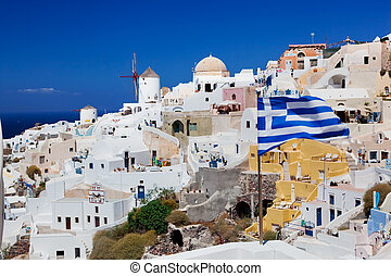 Oia town on Santorini island, Greece. Waving Greek flag -...