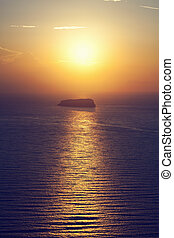 A lonely island, rock on the sea at sunset. Santorini,...
