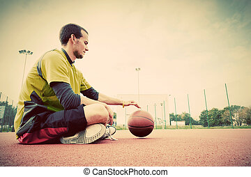Young man on basketball court. Sitting and dribbling with...