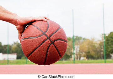 Young man on basketball court Sitting and dribbling with...