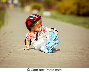 two year old girl in roller skates and a helmet - two year...
