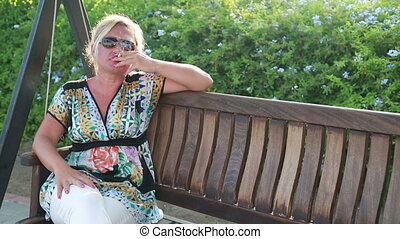 Woman smoking cigarette at the park