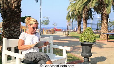 woman using digital tablet - Woman sitting on a park bench...