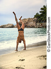 Fit muscular man doing a handstand on the beach - Fit...